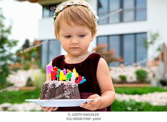Female toddler carrying birthday cake with candles in garden