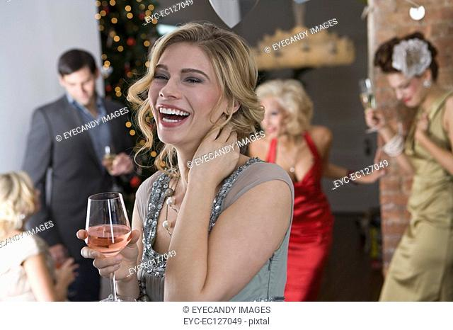 Portrait of laughing blonde woman having a drink at holiday party with friends