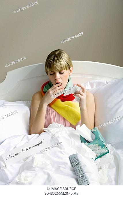 A woman in bed with a cold