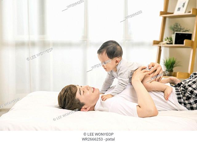 Side view of young father lying down on bed playing with his baby son