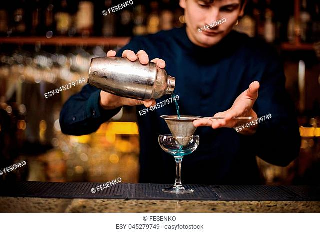 young barman in a blue shirt filters through a strainer an alcohol cocktail Blue Lagoon