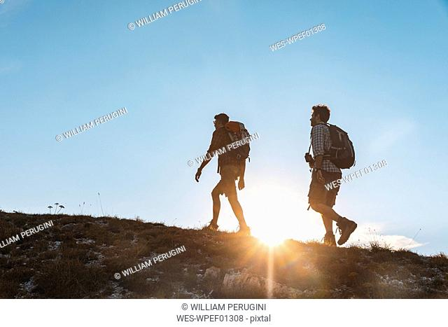 Italy, Monte Nerone, two men hiking in mountains at sunset