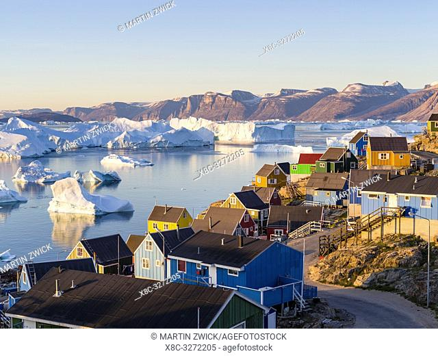View of fjord full of icebergs towards Nuussuaq (Nugssuaq) peninsula during midnight sun. The town Uummannaq in the north of West Greenland