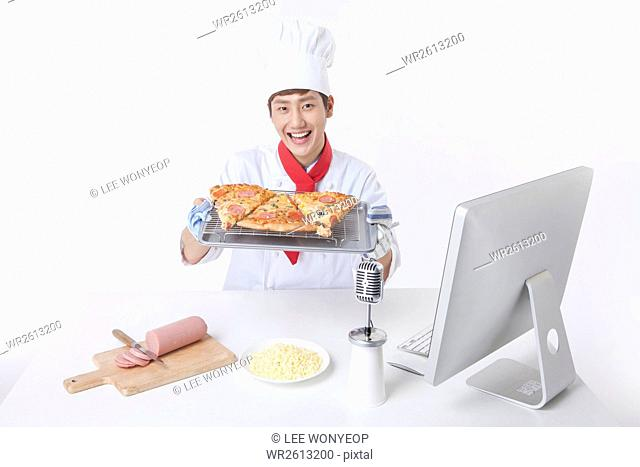 Portrait of young male cook showing pizza during broadcast