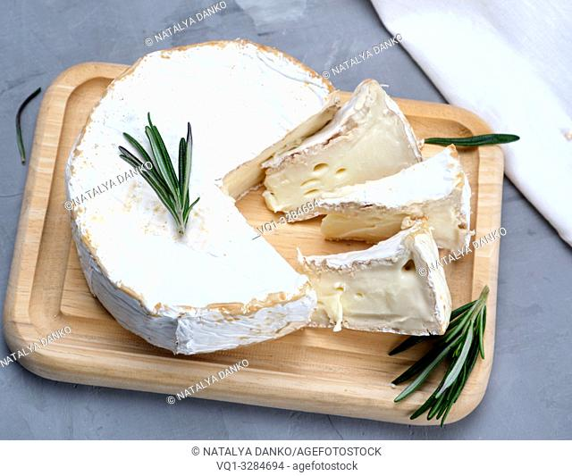 round brie cheese on a wooden board, gray background , top view