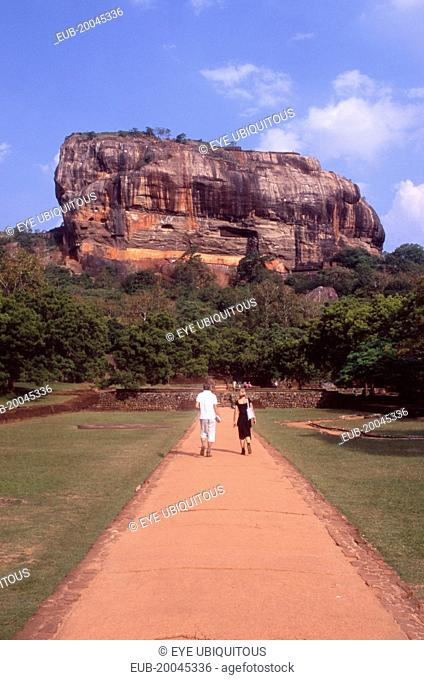 View towards huge monolithic rock site of fith century citadel. Also called Lion Rock. Tourist couple on path through gardens in the foreground