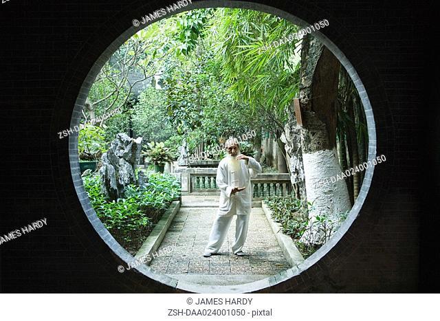 Elderly man wearing traditional Chinese clothing doing Tai Chi