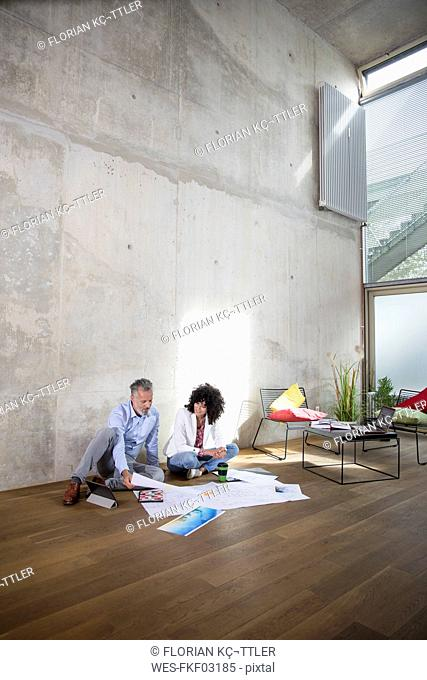 Businessman and businesswoman sitting on the floor in a loft discussing documents