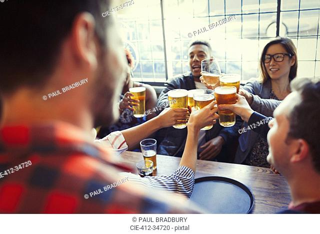 Friends celebrating, toasting beer glass at bar table