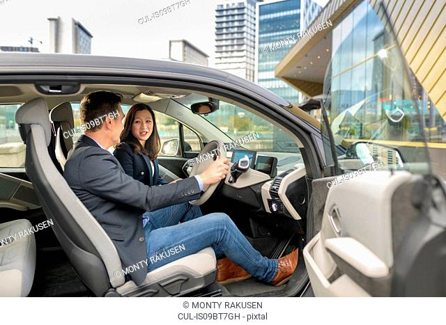 Man and woman sitting in electric car, Manchester, UK