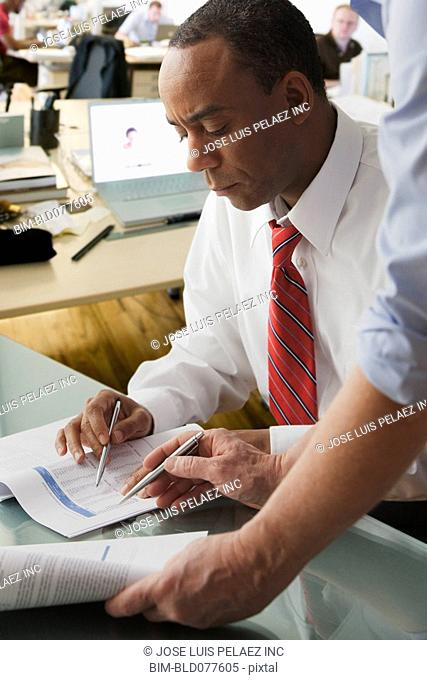 African businessman looking at paperwork with co-worker