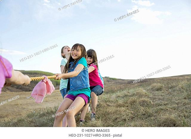 Schoolgirls playing tug-of-war during field trip
