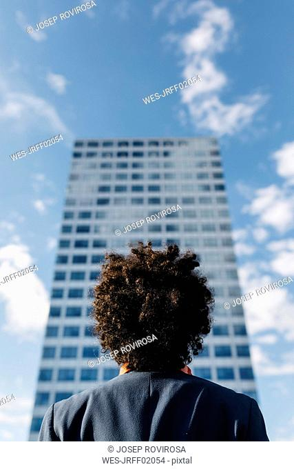 Spain, Barcelona, rear view of a young businessman looking at office block in the city