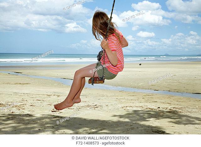 Young Girl on Rope Swing under Pohutukawa Tree, Waihi Beach, Coromandel, North Island, New Zealand