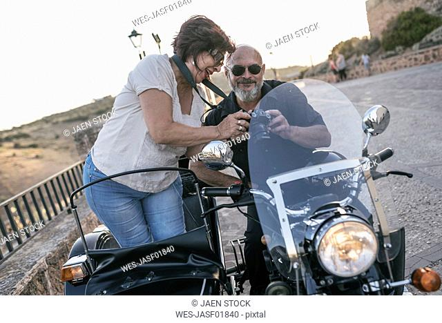 Spain, Jaen, mature couple with motorcycle with a sidecar looking at camera