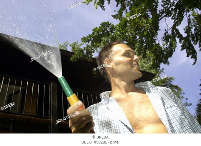 man looking while holding a garden hose