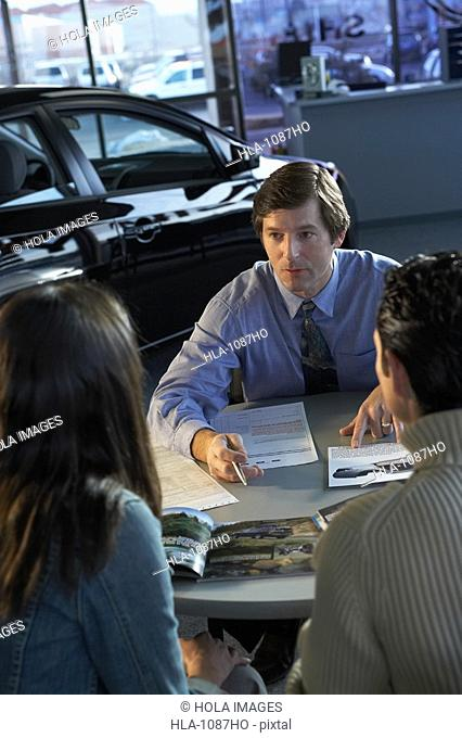 Car salesman giving details about a car to a couple in a car showroom