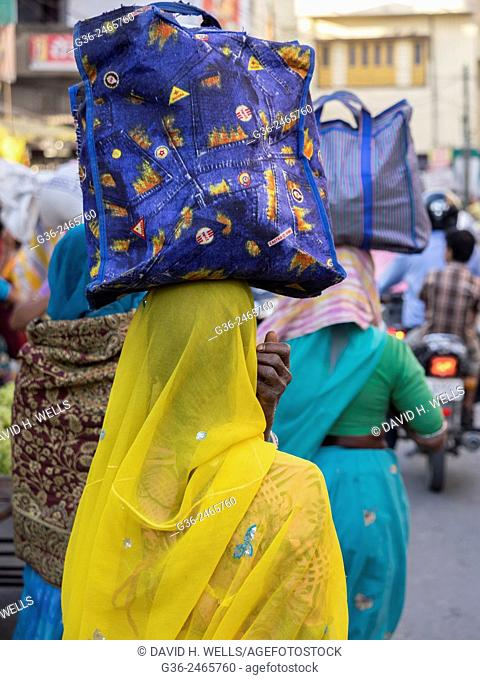 Woman carrying container on crowded street in Udaipur, Rajasthan, India