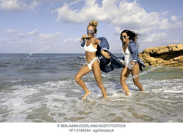 Two women running in sea water at beach, Chersonissos, Crete, Greece