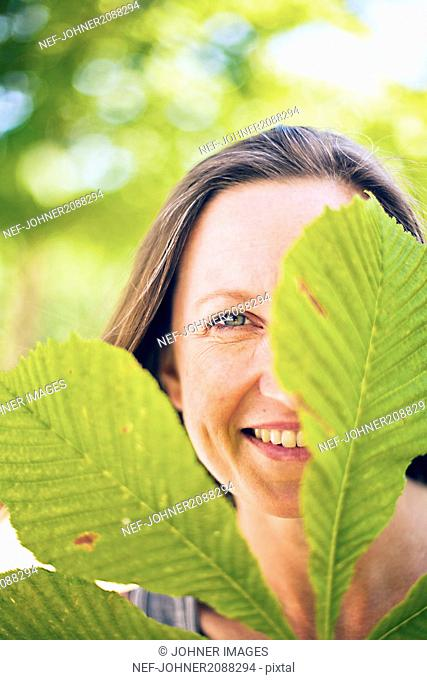 Portrait of smiling woman with chestnut leaf in foreground