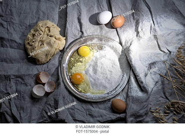 Directly above shot of eggs and flour on fabric at table