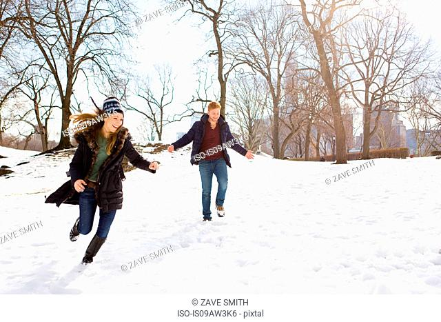 Young couple running in snowy Central Park, New York, USA