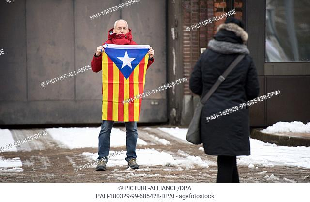 29 March 2018, Germany, Neumuenster: Santi from Catalonia holding a Catalonian flag having his picture taken by his friend in front of the correctional facility...