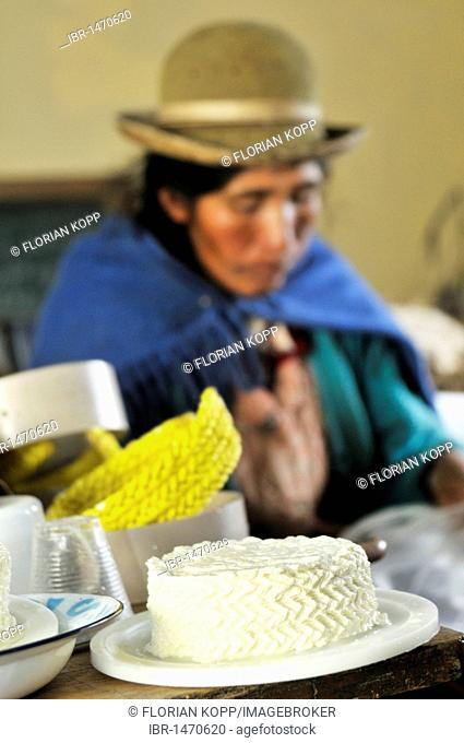 Production of fresh cheese in the Penas Valley, finished cheese and woman in traditional dress of the Quechua in the Departamento Oruro, Bolivia, South America