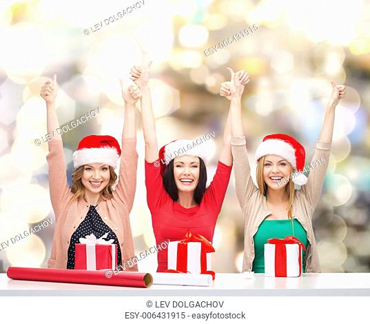 christmas, holidays, celebration, decoration and people concept - smiling women in santa helper hats with decorating paper and gift boxes showing thumbs up over...