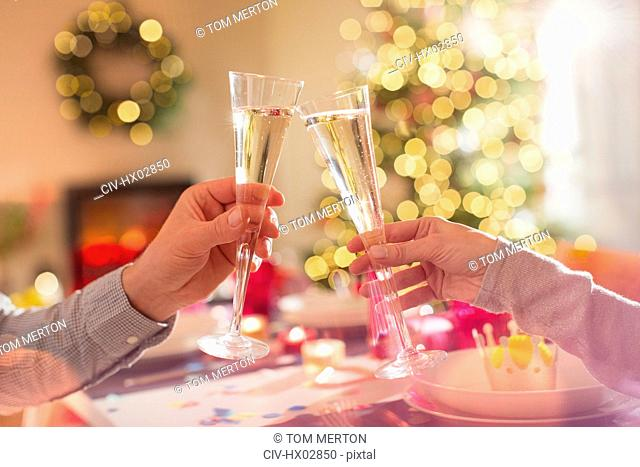 Couple toasting champagne flutes at Christmas dinner table