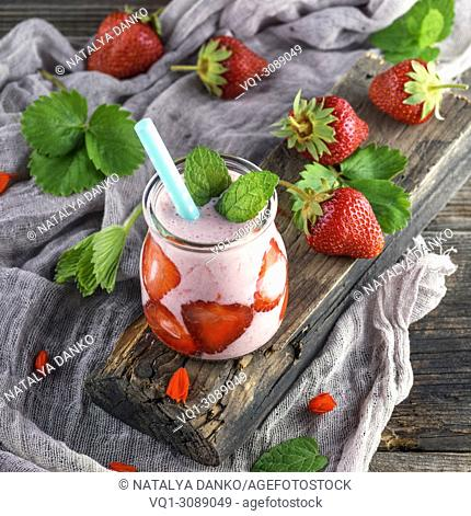 smoothies of fresh strawberries in a glass jar , close up