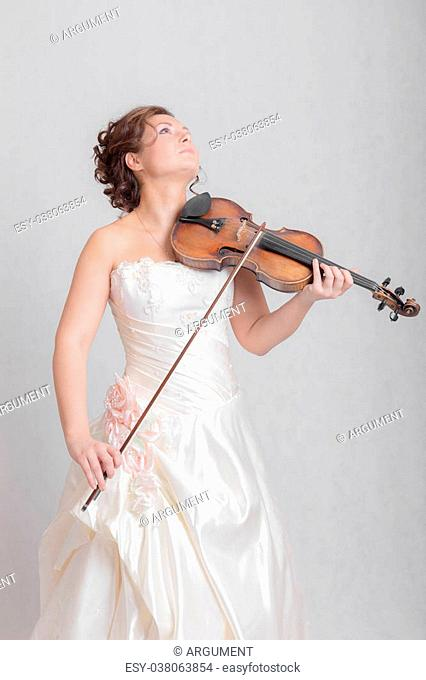girl in white dress playing the violin