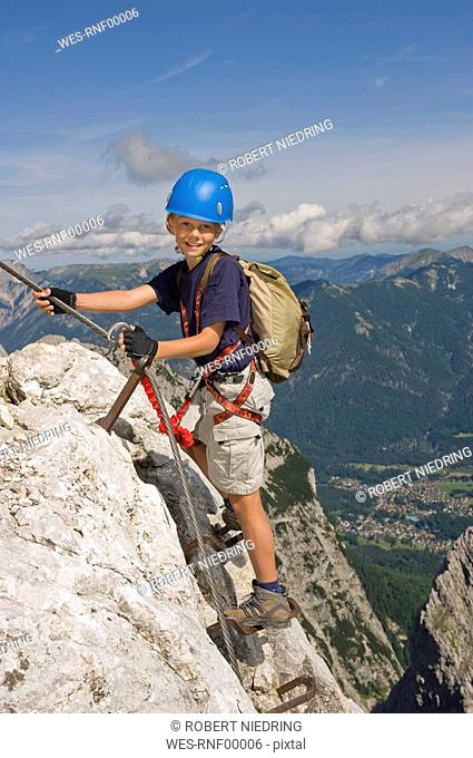 Germany, Garmisch-Partenkirchen, Alpspitz, Boy 10-11 climbing rock face on ladder, smiling, portrait