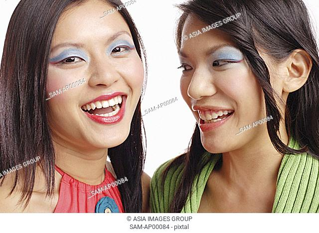 Two women with make up smiling