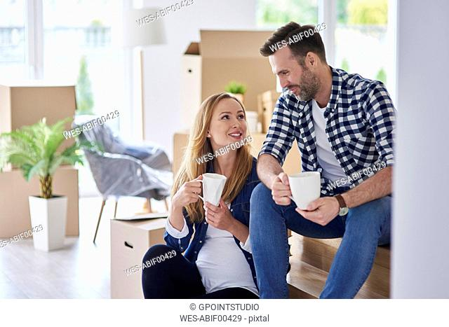 Man and pregnant woman moving into new flat having a coffee break