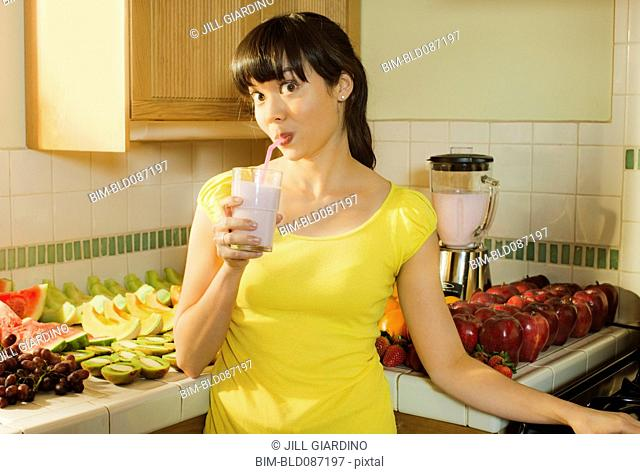 Mixed race woman drinking smoothie in kitchen