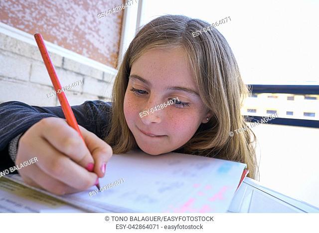 Happy student girl doing her homework on table
