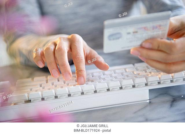 Mixed race woman shopping online with credit card