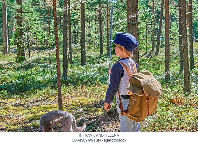 Boy wearing retro clothes walking with dog in forest