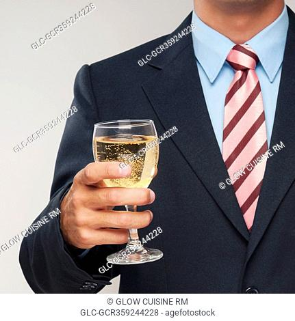 Mid section view of a businessman holding a glass of white wine