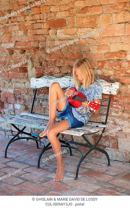 Girl sitting on bench playing ukulele, Buonconvento, Tuscany, Italy