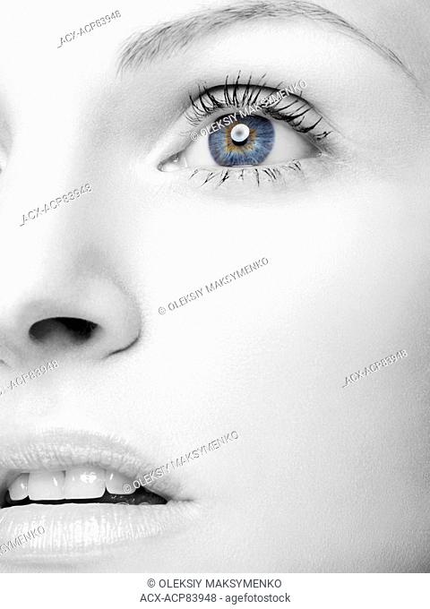 Closeup of a beautiful young woman black and white face with blue eyes