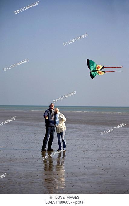 A senior couple flying a kite on the beach