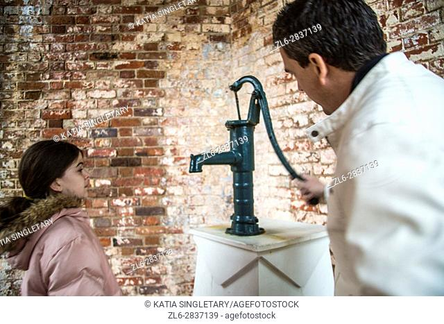 Handsome caucasian dark hair man in his 40's 50's pumping an old cast iron fountain and his daughter drinking out of the fountain in an old fort museum
