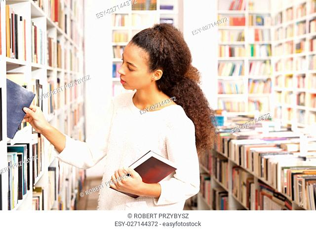 woman looking for a book on a shelf in the library. borrowing books at the library. book woman shopping in a bookstore. the girl in the library
