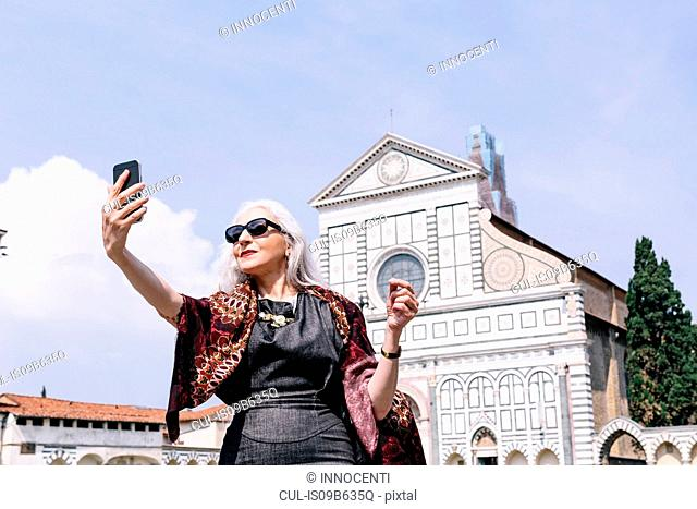 Stylish mature woman taking selfie in front of Santa Maria Novella church, Florence, Italy