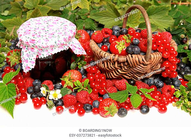 Strawberries, red currants, raspberries and blueberries on white with a basket and a marmalade jar