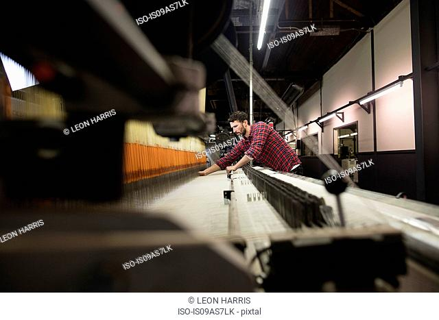 Young male weaver working at old weaving machine in textile mill