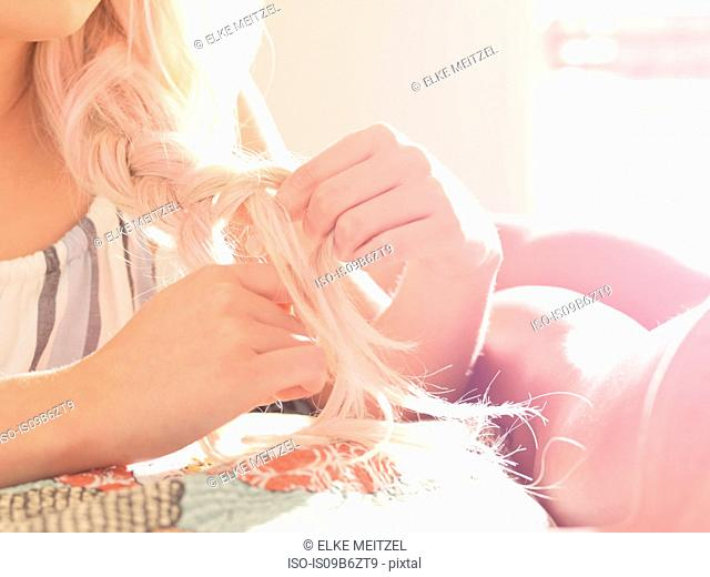 Young woman plaiting hair, female friend lying on bed beside her, close-up, mid section