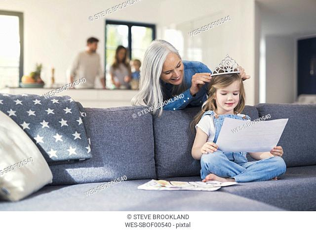 Grandmother playing with granddaughter, puuting crown on her head